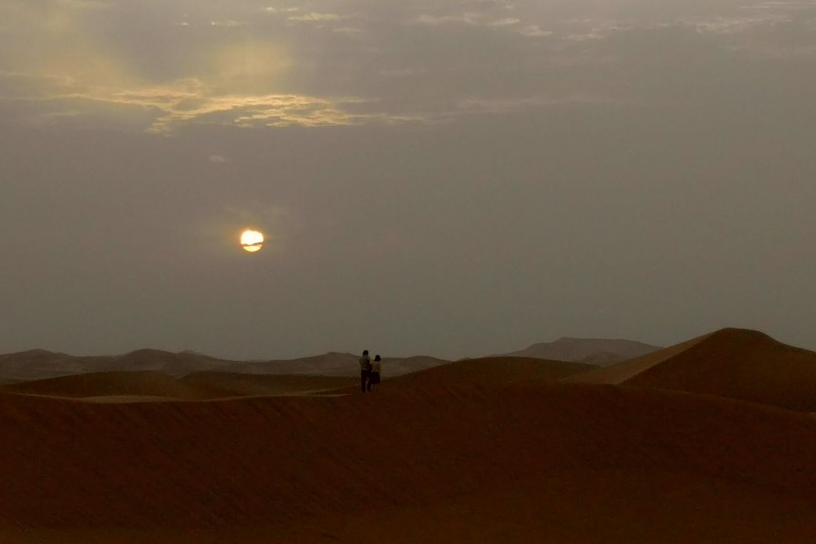 Two people hiking through the Sahara Desert